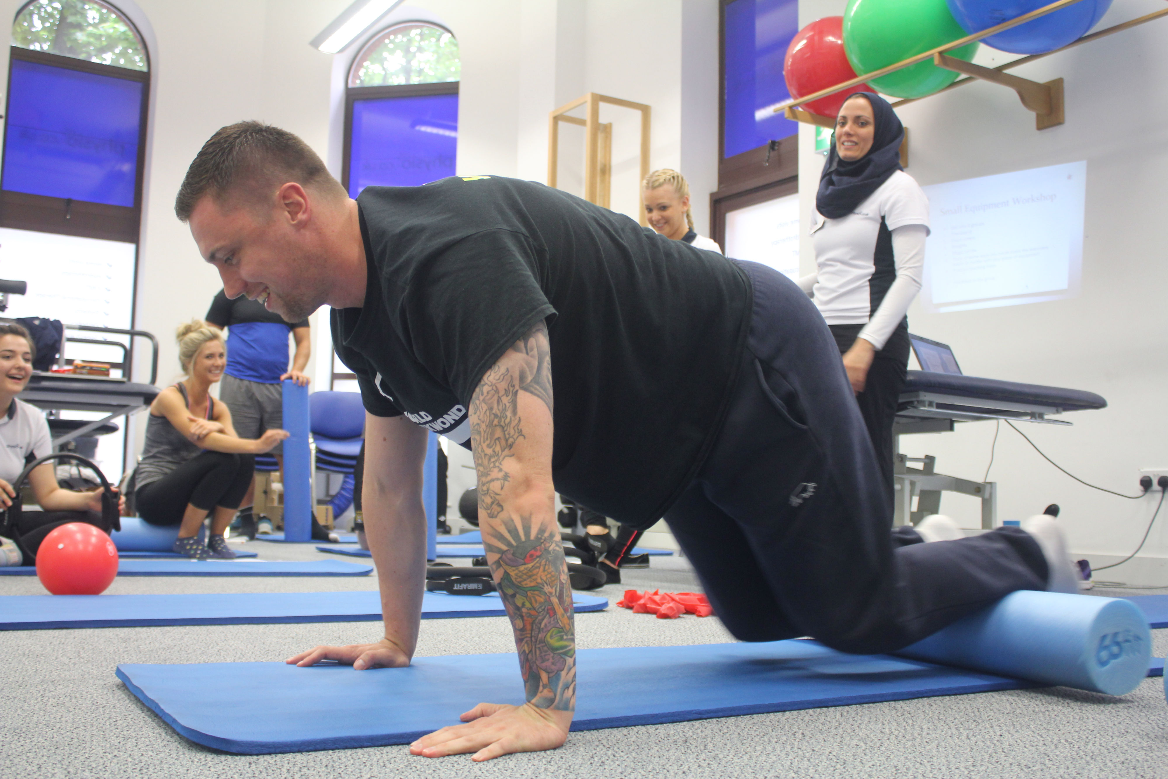 Man crouched on mat doing pilates